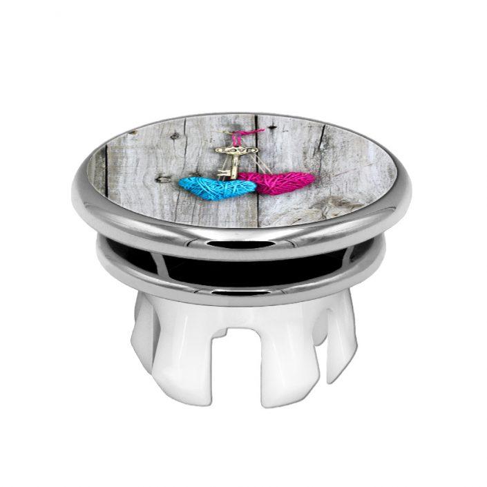 Eine Waschbeckenüberlaufrosette der Marke Knoppo mit dem Design Modell Schlüssel zum Herzen
